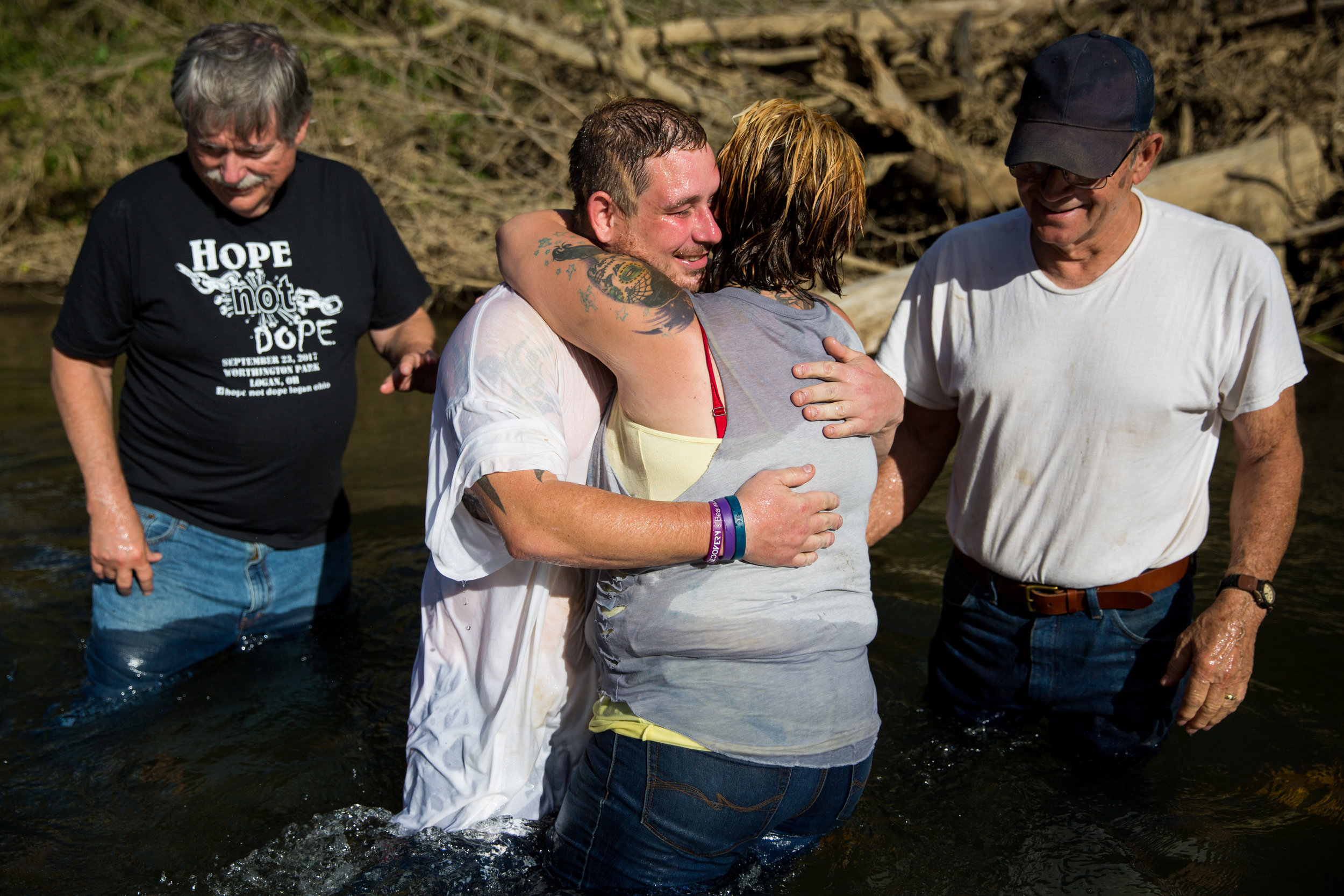 Whitney hugs Jeremy after his baptism by Pastor Bruce Livingston, left, and Whitney's adoptive father, Larry Swart, right. Jeremy has known Pastor Livingston since he was a child and sees him as a sort of father figure.