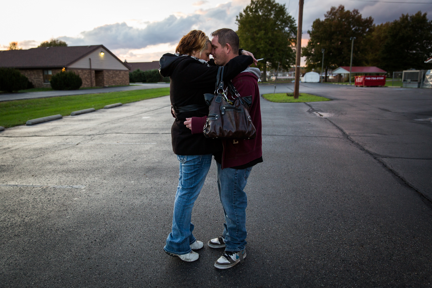 Whitney Johnson and Jeremy Rhoades hold each other in the parking lot outside of First Baptist Church in Logan, Ohio, before Celebrate Recovery, a Christ-based support group for recovering addicts.