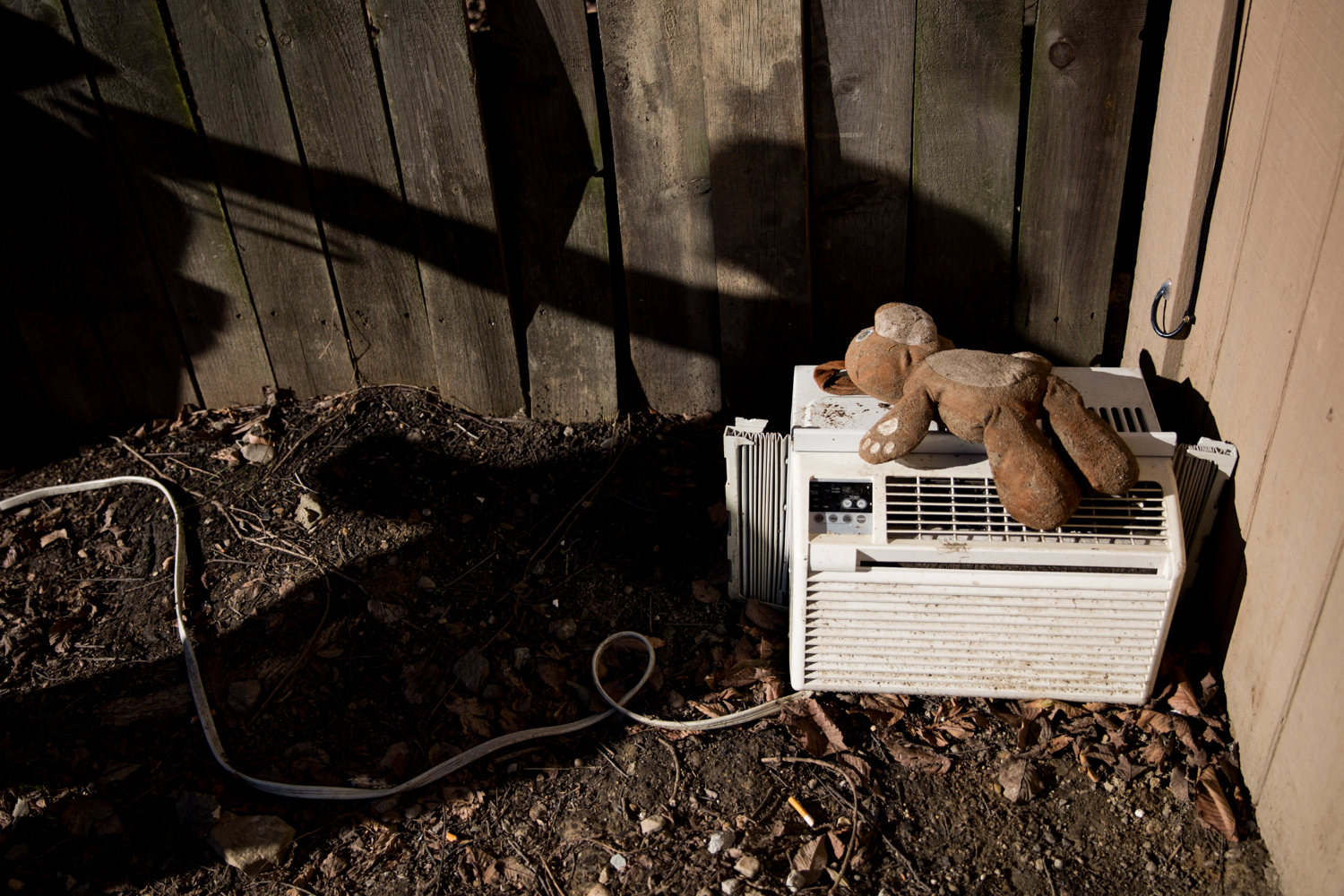 A stuffed animal that Paisley left out in the rain dries off on top of a discarded air conditioning unit.