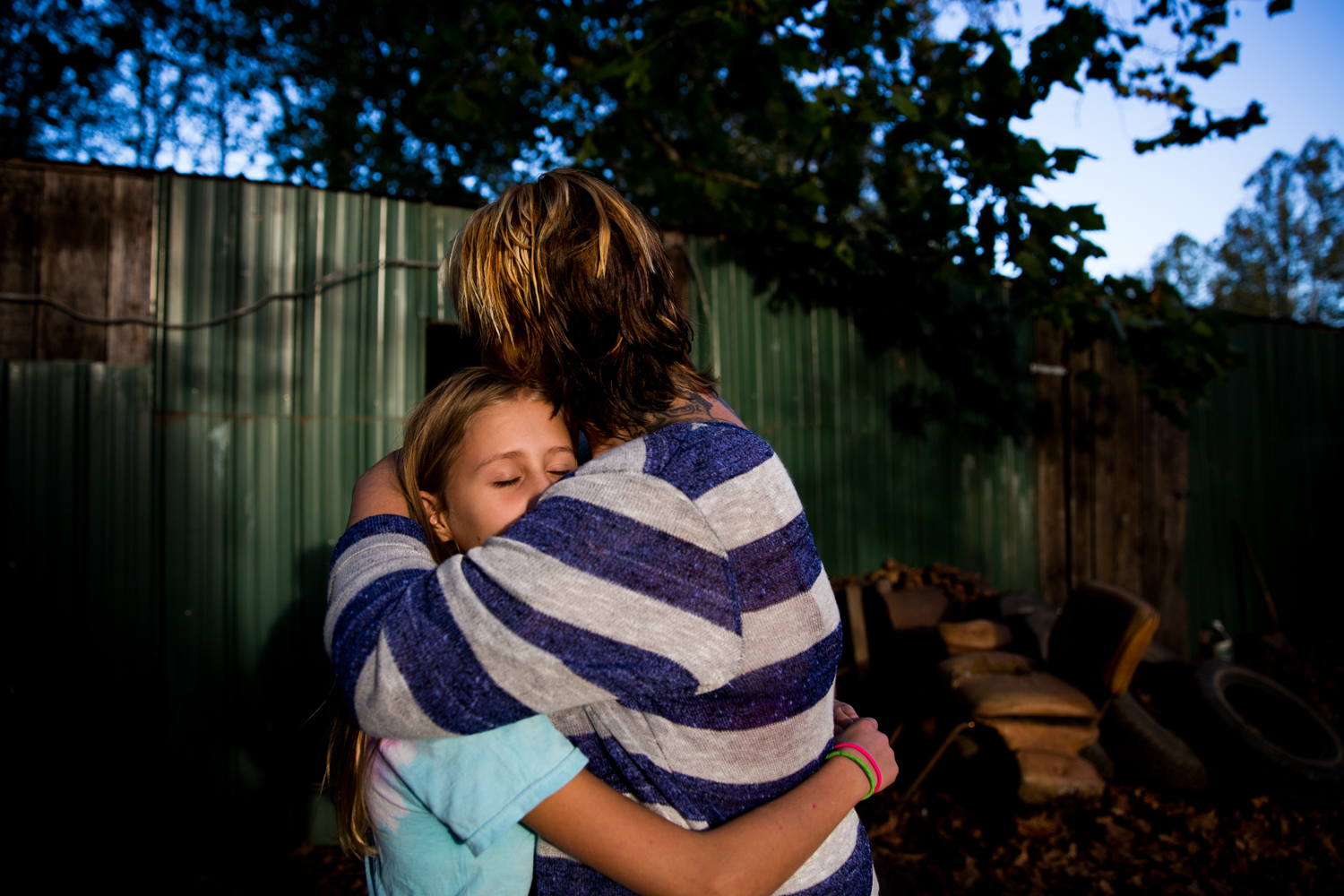 Whitney hugs her adoptive sister, Angel, at their family's property off of old route 33 near Nelsonville. When Whitney moved away from the Swarts' house she returned to an abusive husband, and her relationship with her adoptive family became strained. After getting clean and starting a new relationship she was able to return to her adoptive family's home to visit for the first time in months.