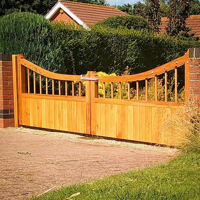 Bespoke curved rail solid English Oak gates. Native air dried oak,hand finished in UV resistant Osmo Oil.