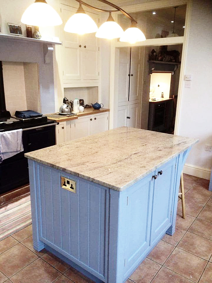 """Bespoke island, finished in Little Greene """"James"""" with granite top, integrated power points, German soft close hardware, and an all real oak interior."""