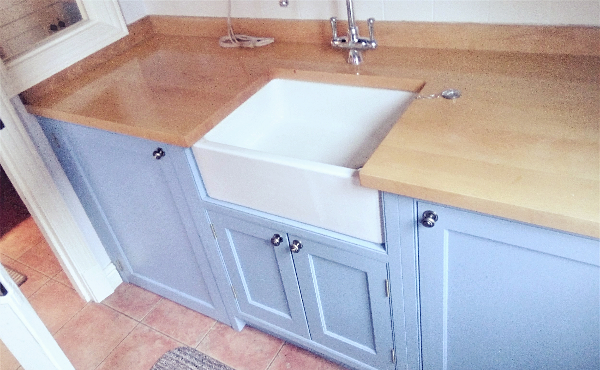 Bespoke fitted Belfast sink unit, with concealed washer and dryer housings either side.