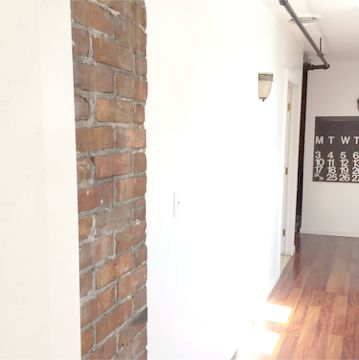 Our back hallway is long and narrow but has some of the best light and breeze in the entire house! We've left it pretty bare which allows the Stendig Calendar and exposed brick to do the talking!