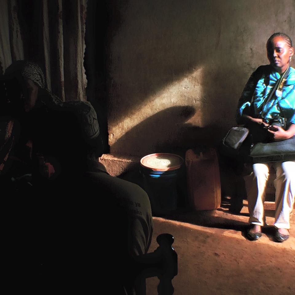 A World Vision Tanzania official watches a community health worker instruct a woman on breastfeeding. (Laura Payton)