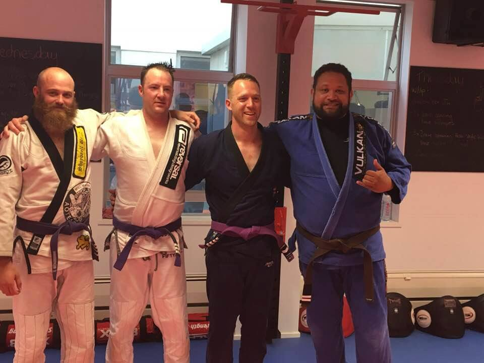 From left to right: Purple belts Andrew, Corrin, and Chris who achieved new tabs, and proud Coach Jay.