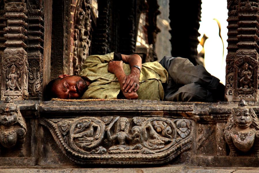 Un homme se repose au pied d'un temple - Katmandou