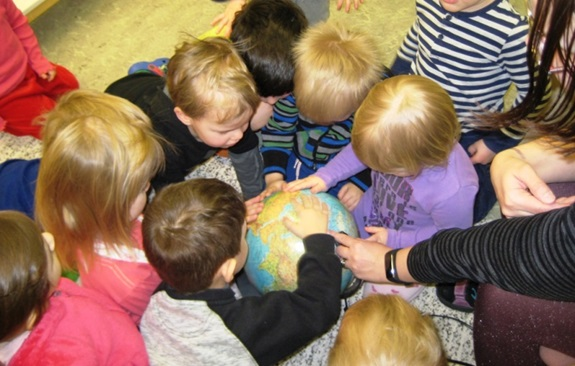 Kids in one of the Finnish kindergartens participating in the scrapbook campaign, curiously searching their scrapbook route on the map and learning about the world