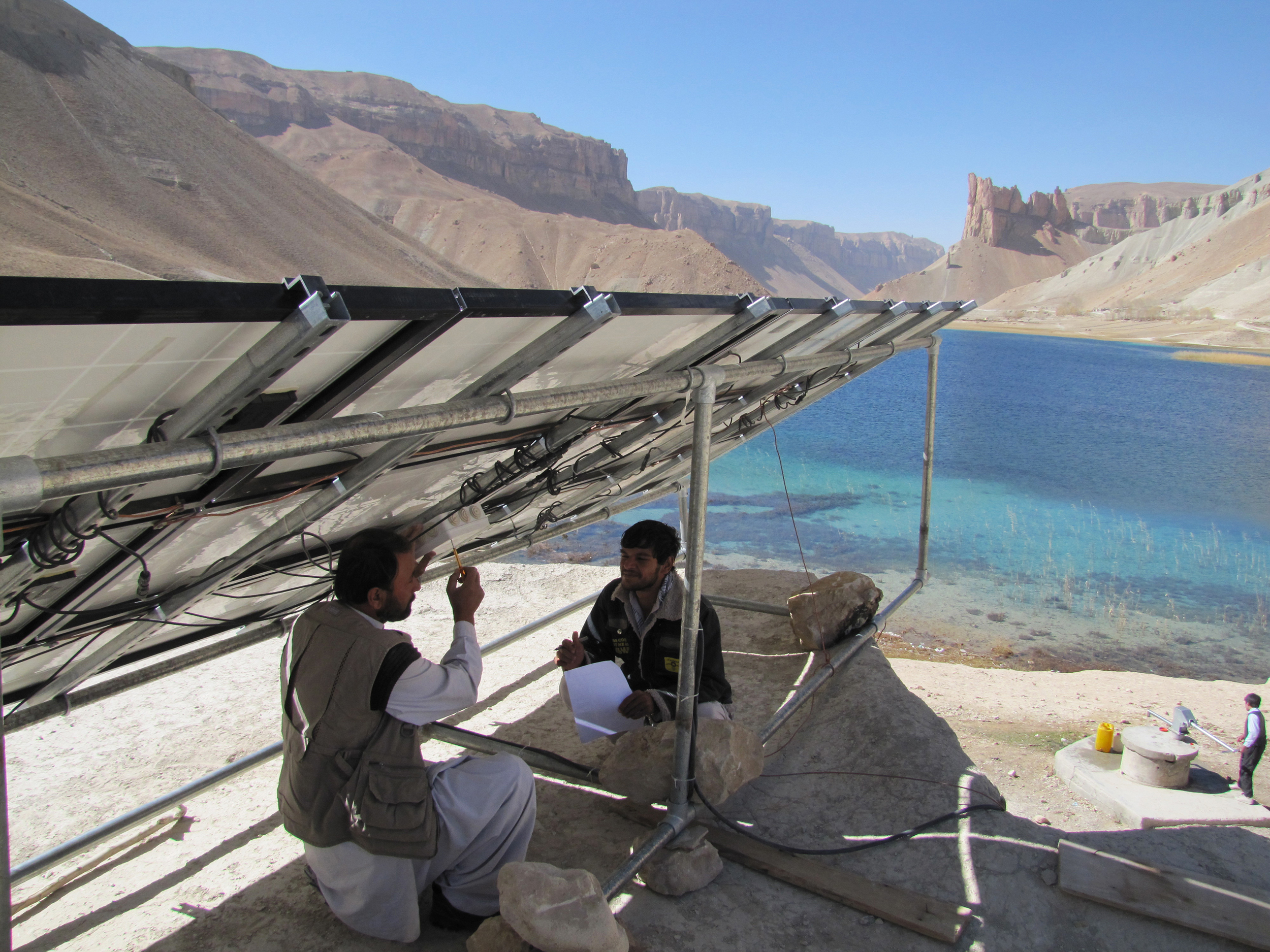 USAID is supporting the electrification of rural schools in Afghanistan, through projects like the Afghanistan Clean Energy Program (ACEP). ACEP created a 2 kW solar-powered system to provide power to the Shaheed Mahmoodi High School in Band-e Amir National Park in Bamiyan Province, benefitting its 621 male and female students. Here Afghan technicians are finishing installation and testing of the solar array. Photo credit: Robert Foster, Winrock International.