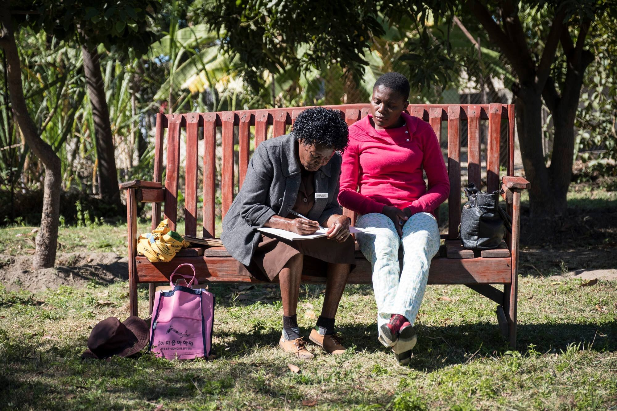 A trained grandmother is helping a patient on the friendship bench