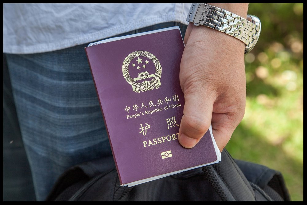 A Chinese national holds a Chinese Passport on May 16, 2014. Chinese officials are finding the regime tightening down on travel documents for them, in order to keep the officials from fleeing China.