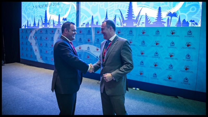 Chris Malo (left), head of global maritime security for Carnival Corporation, and Mick O'Connell (right), director of operational support and analysis for INTERPOL, shake hands.