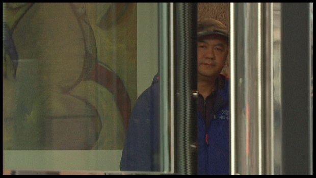 Pei Jia Li peeks through the doors after his hearing at the Immigration and Refugee Board this week in Vancouver. He was ruled 'inadmissible to Canada' for having fraudulent entry and exit stamps in his passport.  (Harold Dupuis/CBC )