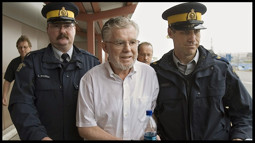 Ernest Fenwick MacIntosh is escorted in custody by RCMP officers at Robert L. Stanfield International Airport in Halifax on Thursday, June 7, 2007 . (Andrew Vaughan/CP)