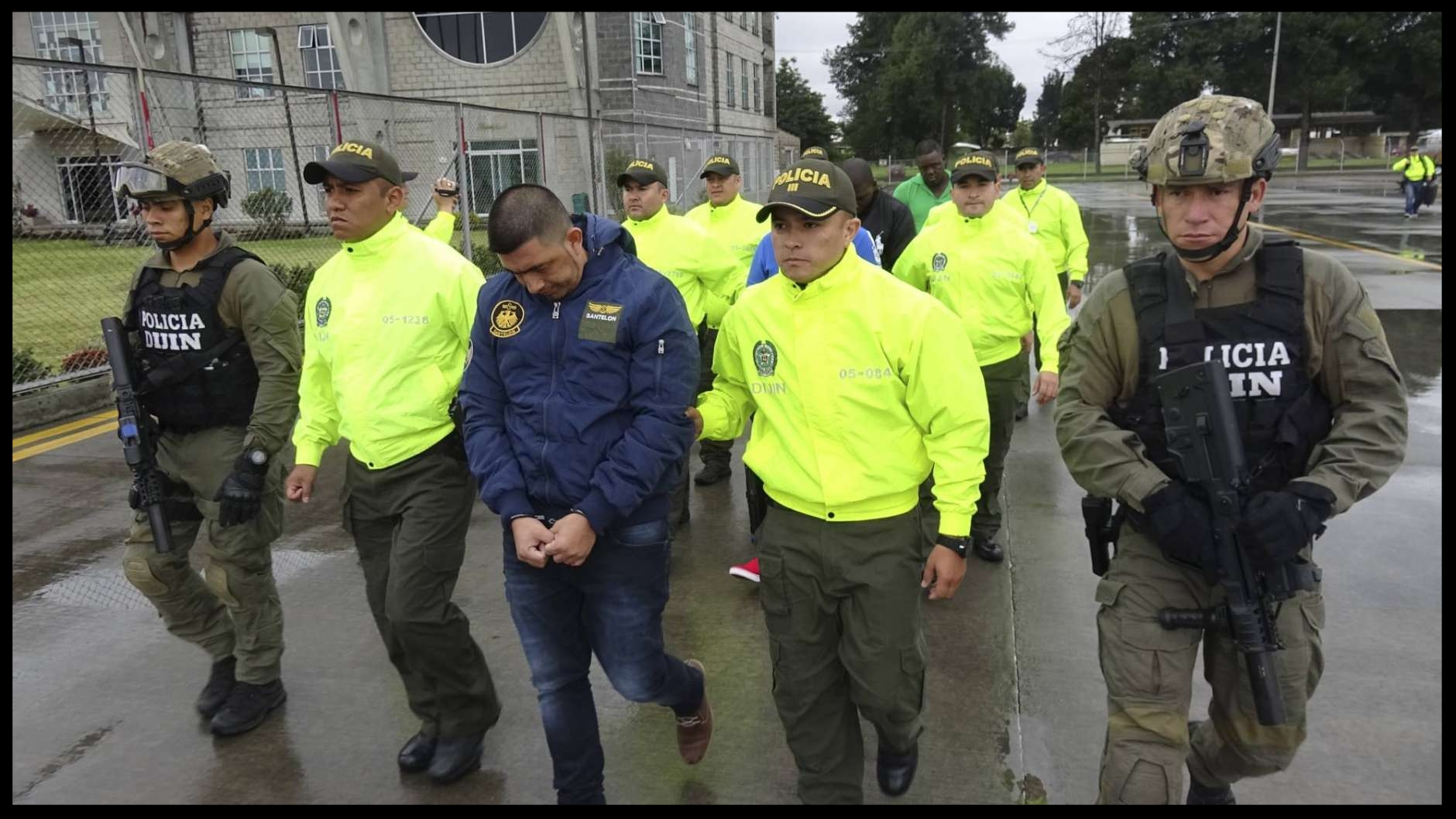 This undated photo released by Colombia's National Police show officers escorting a man who police identify as Ecuadorean drug trafficker Edison Prado after his April 2017 arrest on an indictment by a Florida federal court. A few months after his arrest in a DEA-organized raid, Prado showed up on a list with more than 20 others suspected traffickers wanted for extradition by the U.S. who rebels of the Revolutionary Armed Forces of Colombia, FARC, claimed as jailed members of their now-disbanded insurgency even though they have no known history of rebellion.  (Colombia National Police via AP)