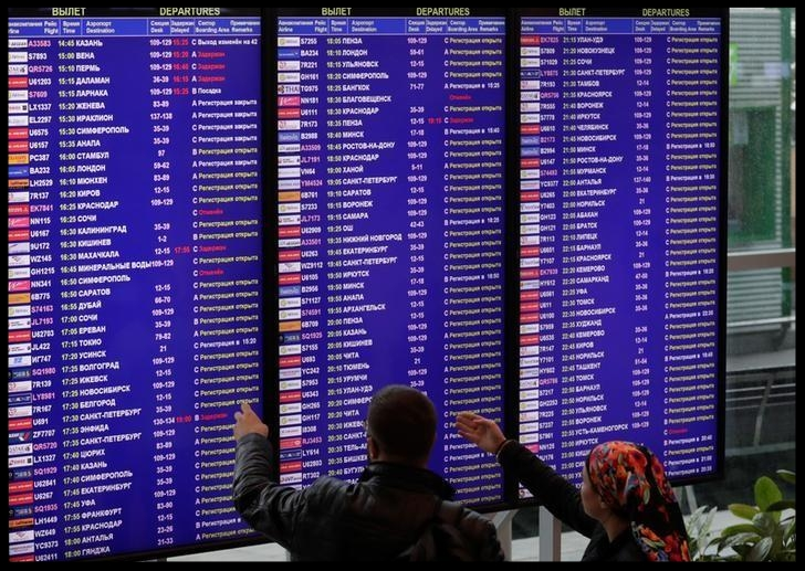Passengers check the departure board at the Domodedovo Airport outside Moscow, Russia September 28, 2017.