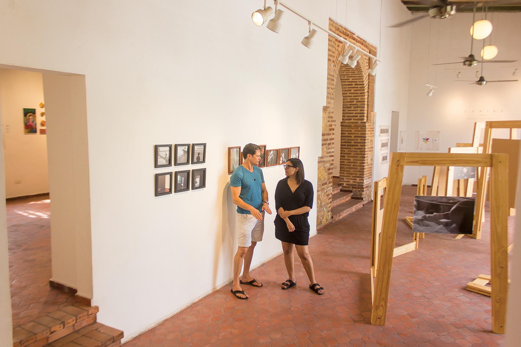Amy Hussein y Raúl Miyar junto a la instalación fotográfica de Karla Read,  Caribe . Fotografía por Carlos Rodríguez.