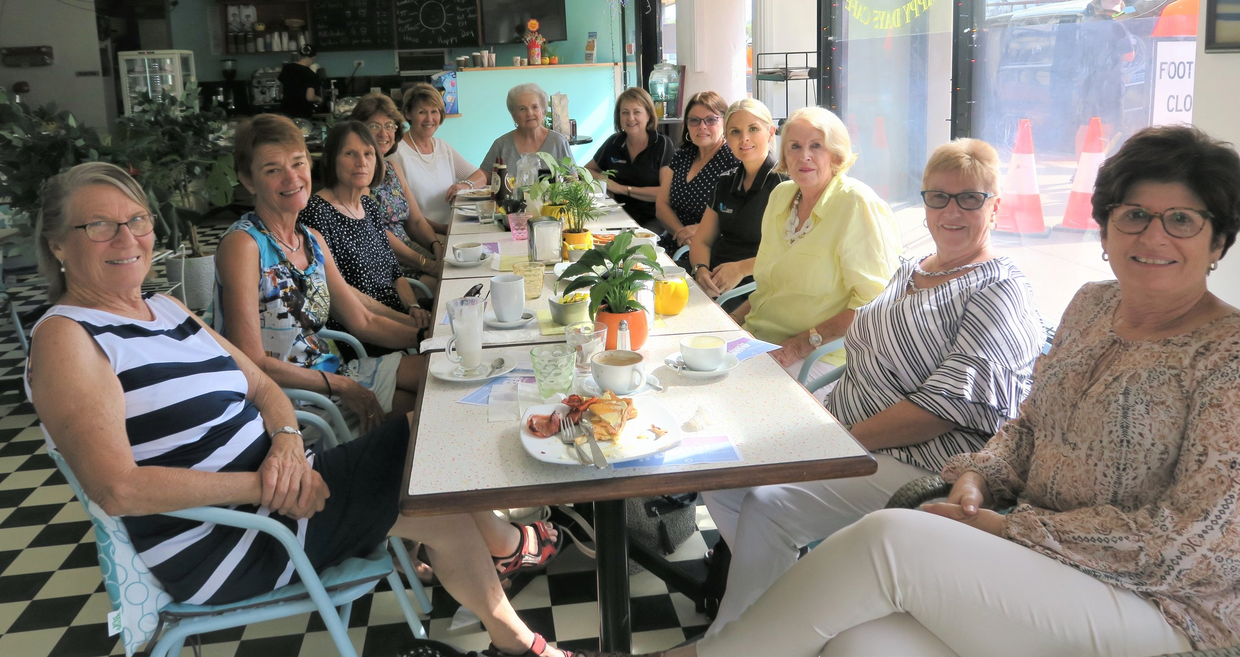 Lesley Muir (Pictured at head of table) gathers with friends at Caloundra's Happy Days Cafe to celebrate International Women's Day.