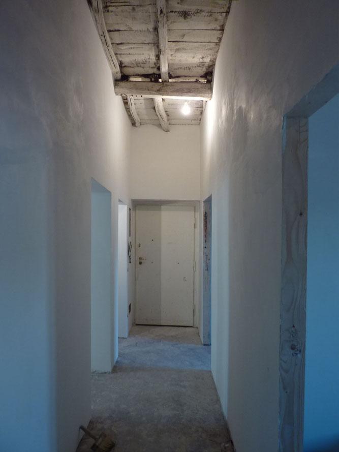 Lo spazio di distribuzione centrale che attraversa tutta l'abitazione, durante i lavori.
