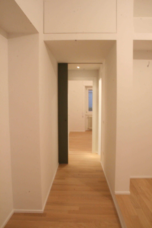 Una delle due camere da letto, con il sistema di vani per gli armadi a incasso e la porta scorrevole sullo sfondo.