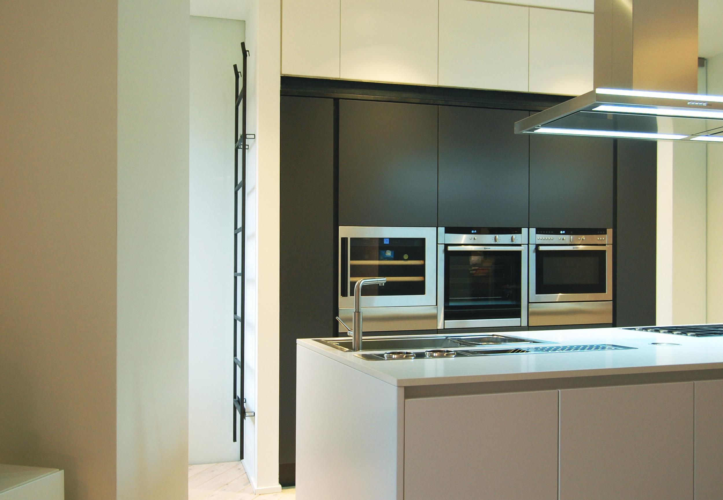La cucina ad isola con alle spalle le colonne attrezzate. Una scala in metallo rimovibile consente l'utilizzo dei vani più alti.