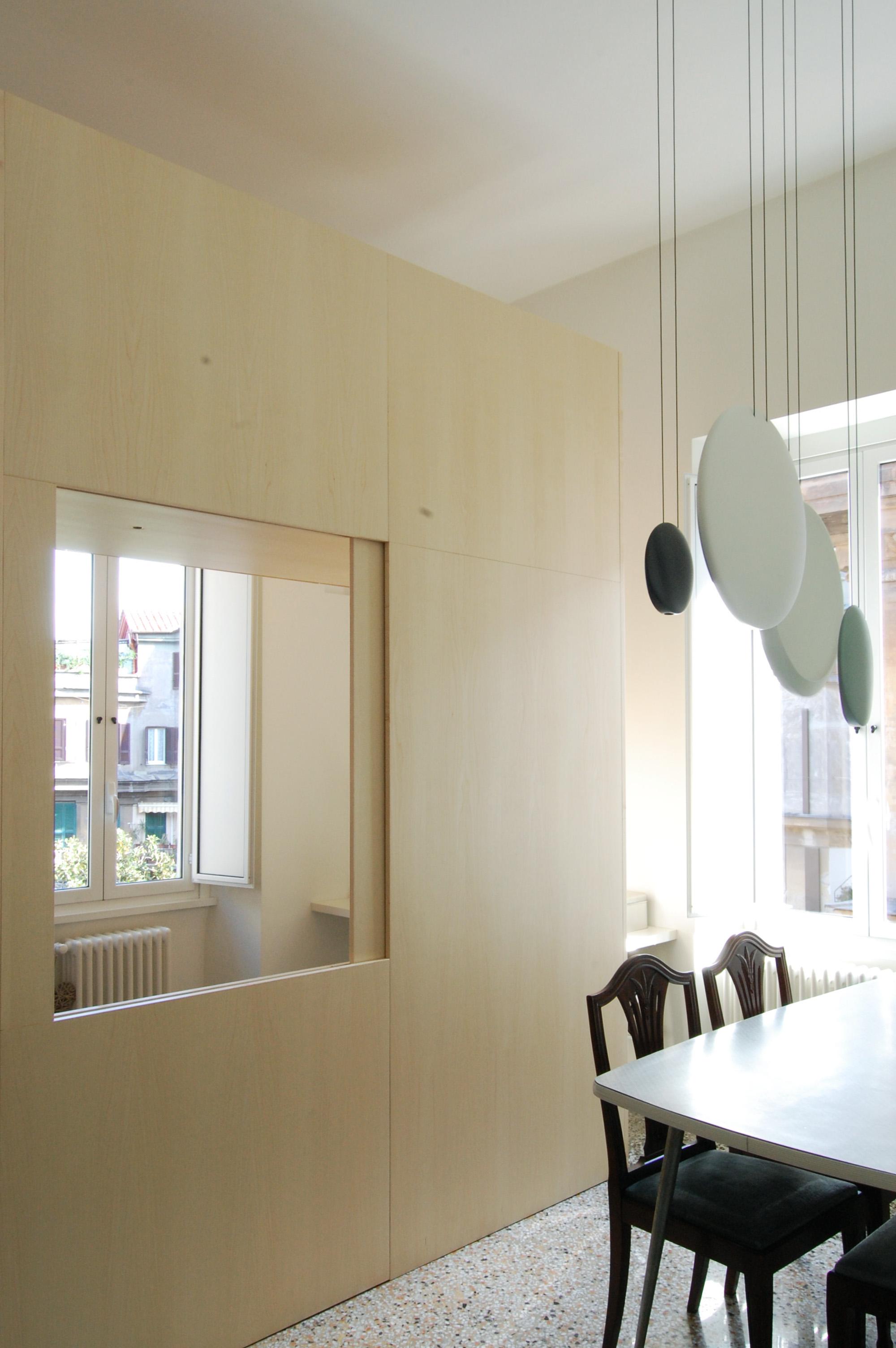Il volume in legno con la sua apertura verso la zona pranzo. Interamente realizzato in falegnameria, è completamente isolabile con pannelli scorrevoli dalla zona living, per essere facilmente utilizzabile come spazio per gli ospiti.