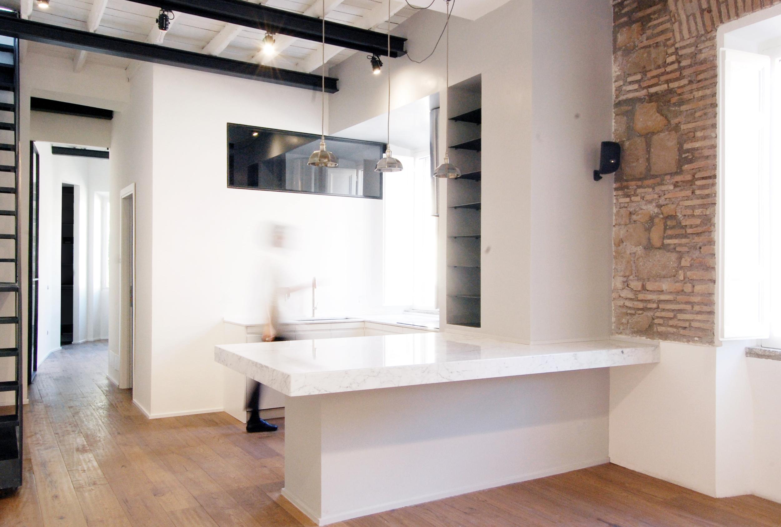 Dalla zona living con lo sguardo rivolto verso la cucina, con il piano in marmo di Carrara a distinguere gli ambiti e la scala sulla sinistra che conduce alla terraza superiore. In fondo, la zona notte.