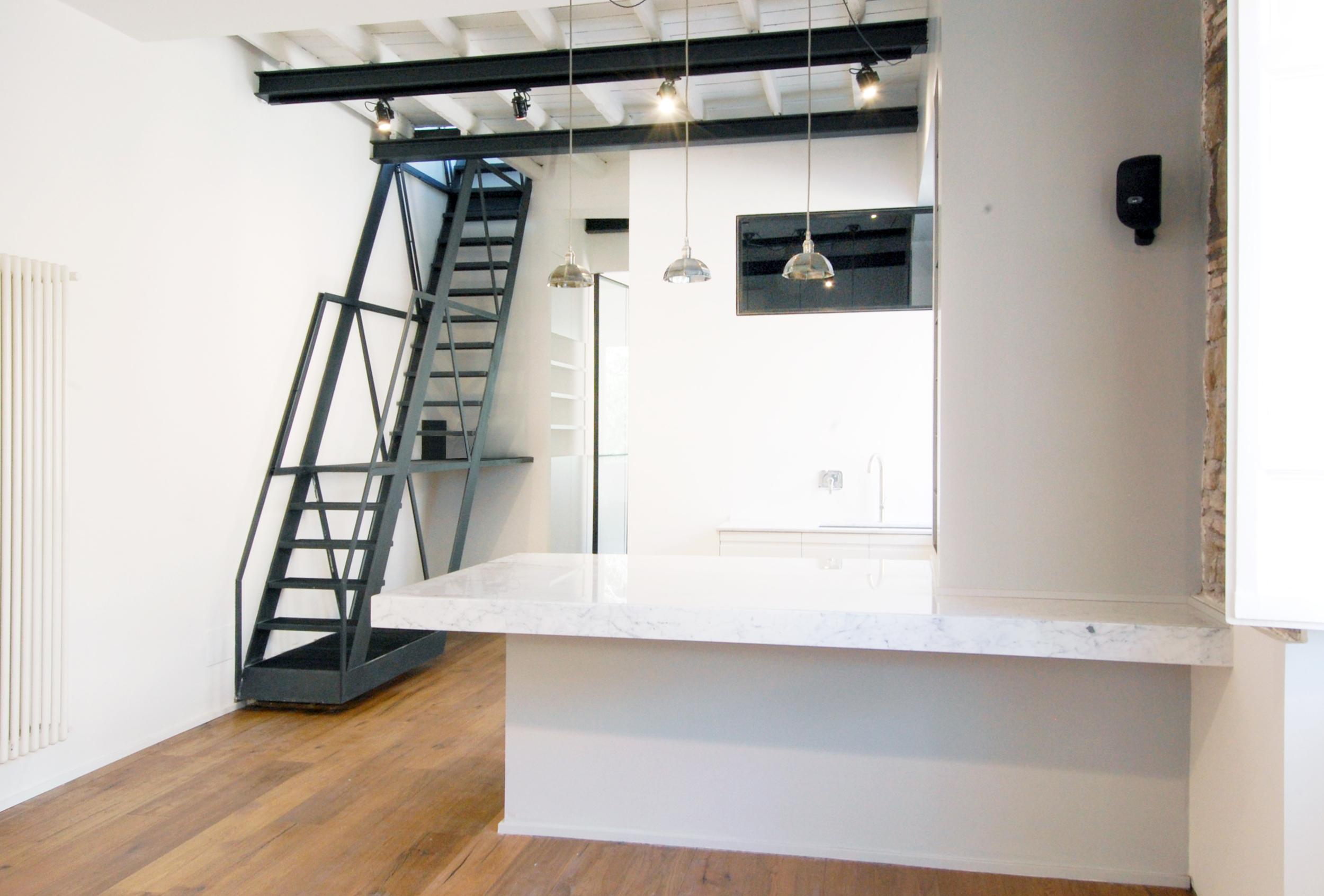 Appena entrati, con il piano in marmo a fare da tavolo in grado di accogliere fino a otto persone a la scala in ferro, un traliccio metallico sospeso che accompagna fino alla terrazza superiore.