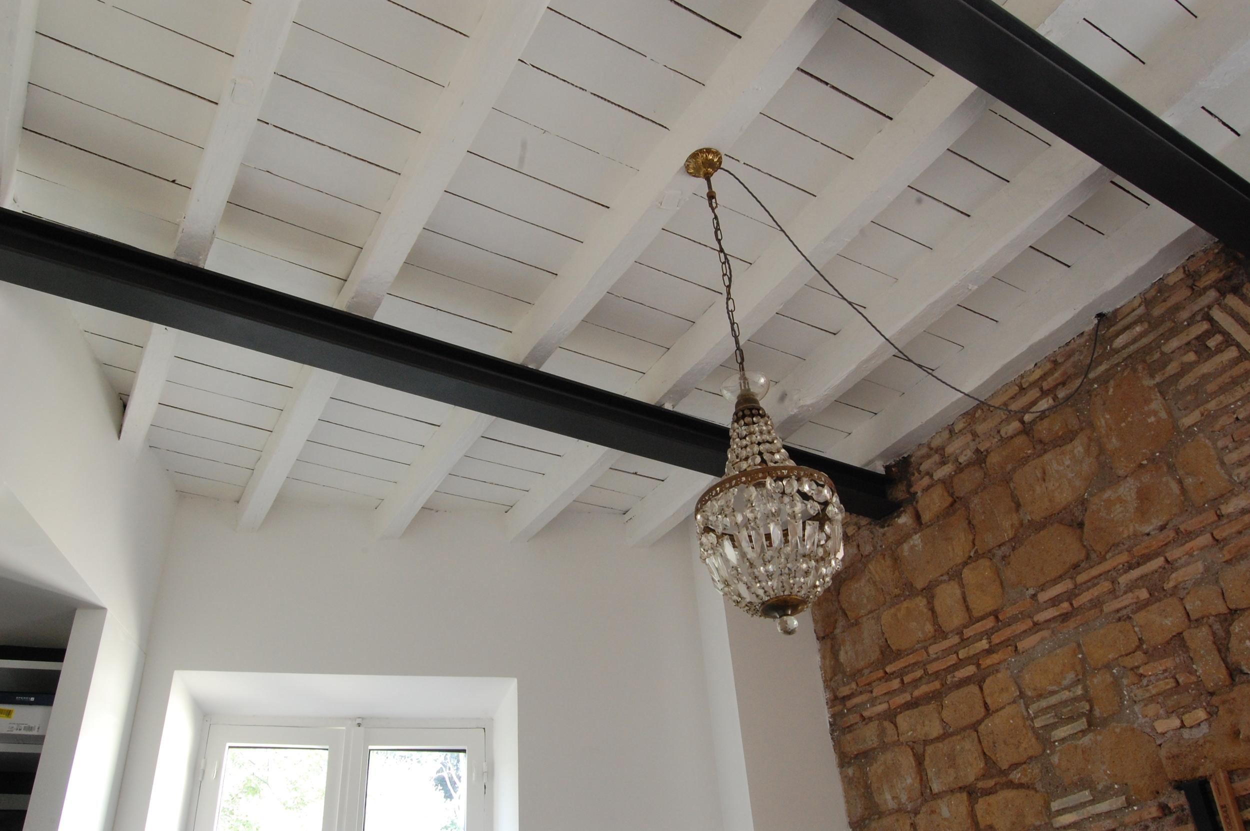 Muratura in vista, travi in ferro e soffitto in legno verniciato bianco. Ambientazione calda e tonalità decise caratterizzano tutta la casa, anche la camera da letto.