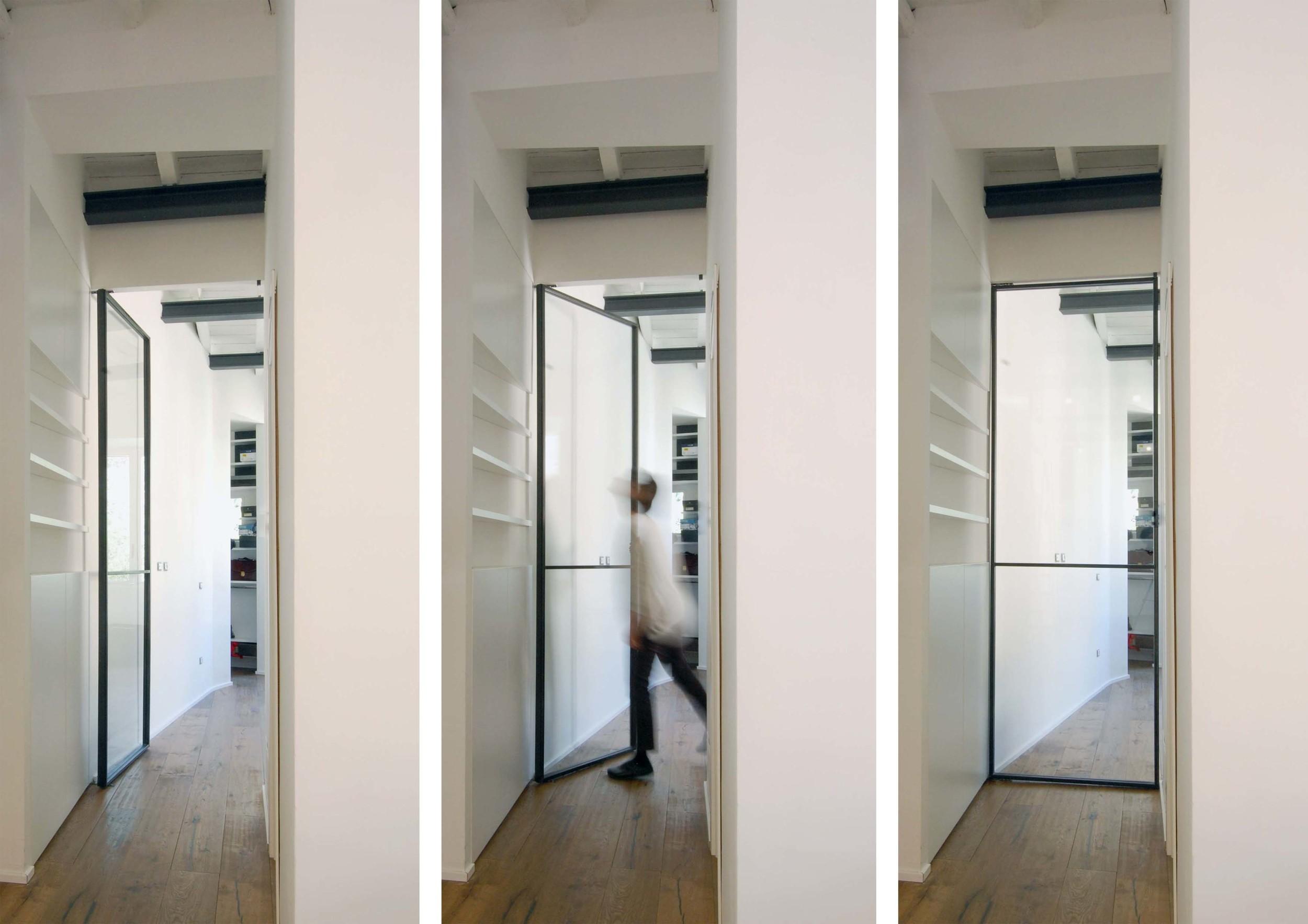 La porta della camera da letto, realizzata con un sottile profilo in ferro e un'ampia superficie vetrata, per dare continuità visiva allo spazio.