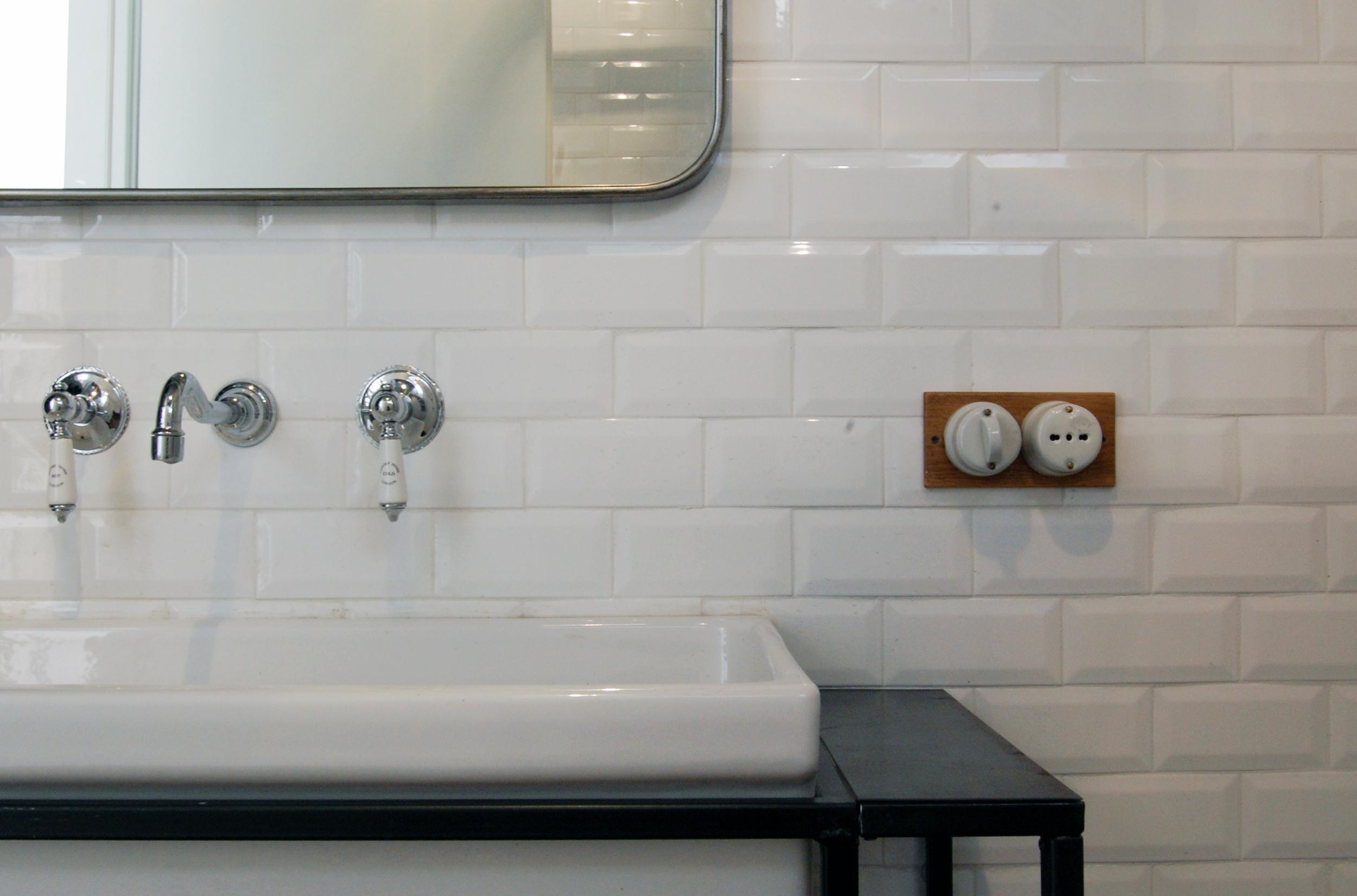 Un dettaglio del bagno, con il lavandino incassato in un struttura metallica e i pulsanti in ceramica su placca in legno.
