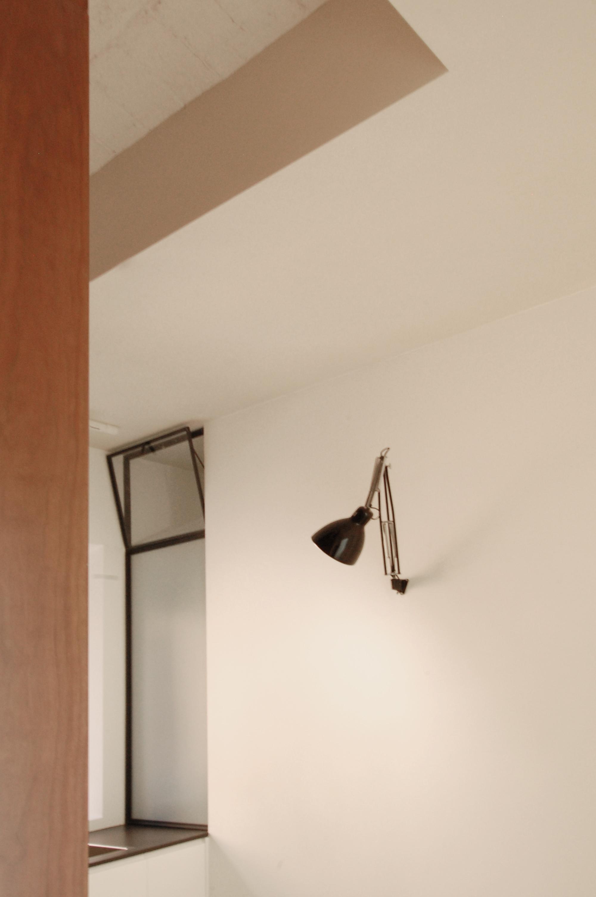 Immagine di dettaglio, con la sottile superficie vetrata a separare doccia e cucina e assicurare luce naturale al bagno.