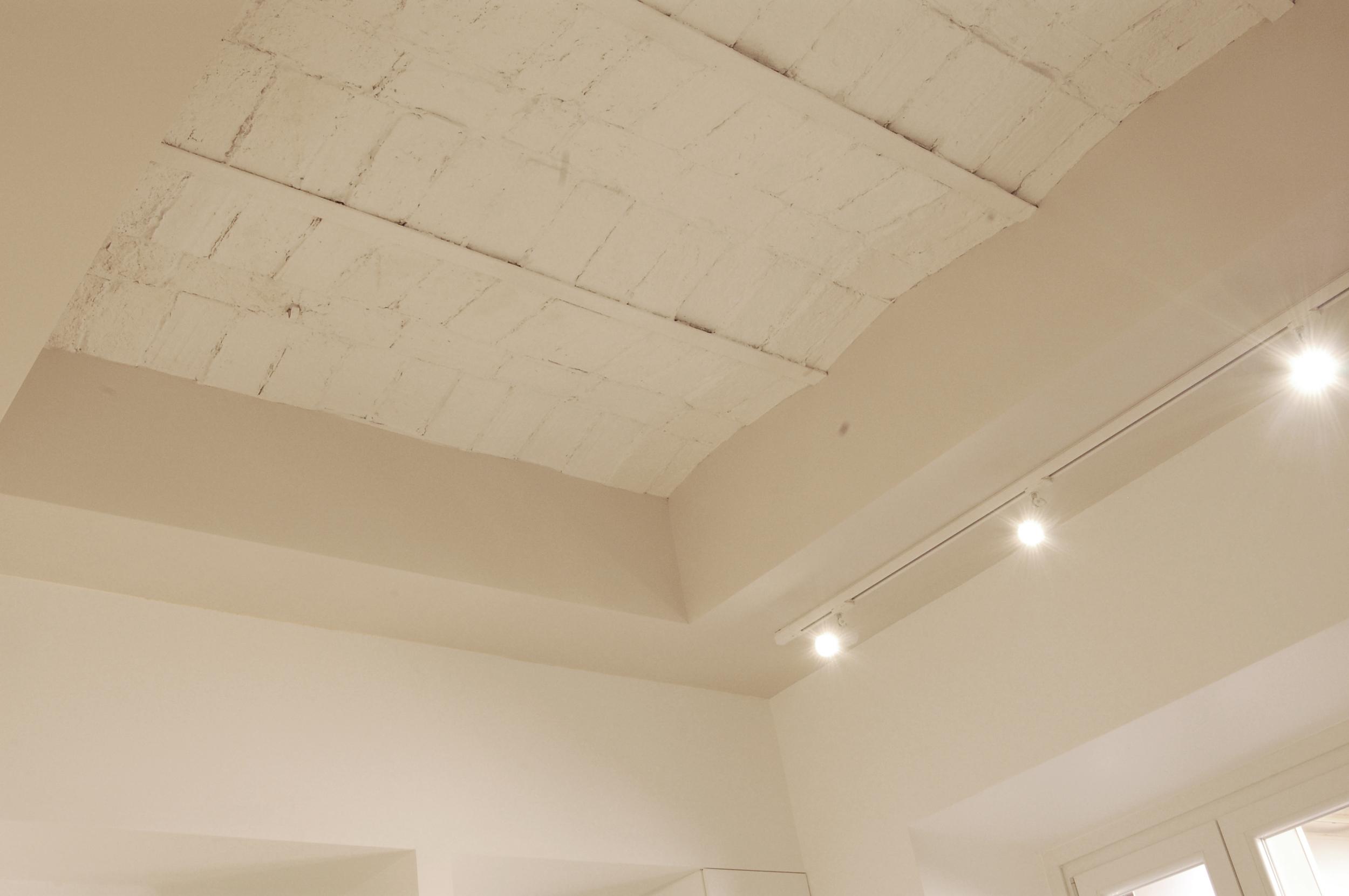 Immagine di dettaglio, con il soffitto a voltine riportato alla luce e posto in risalto dalla scelte cromatiche.