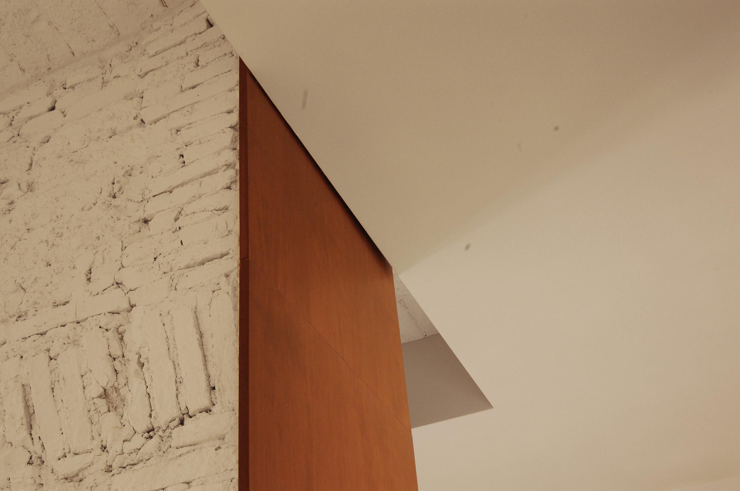 Immagine di dettaglio: geometrie rigorose e materiali caldi per una eleganza discreta.
