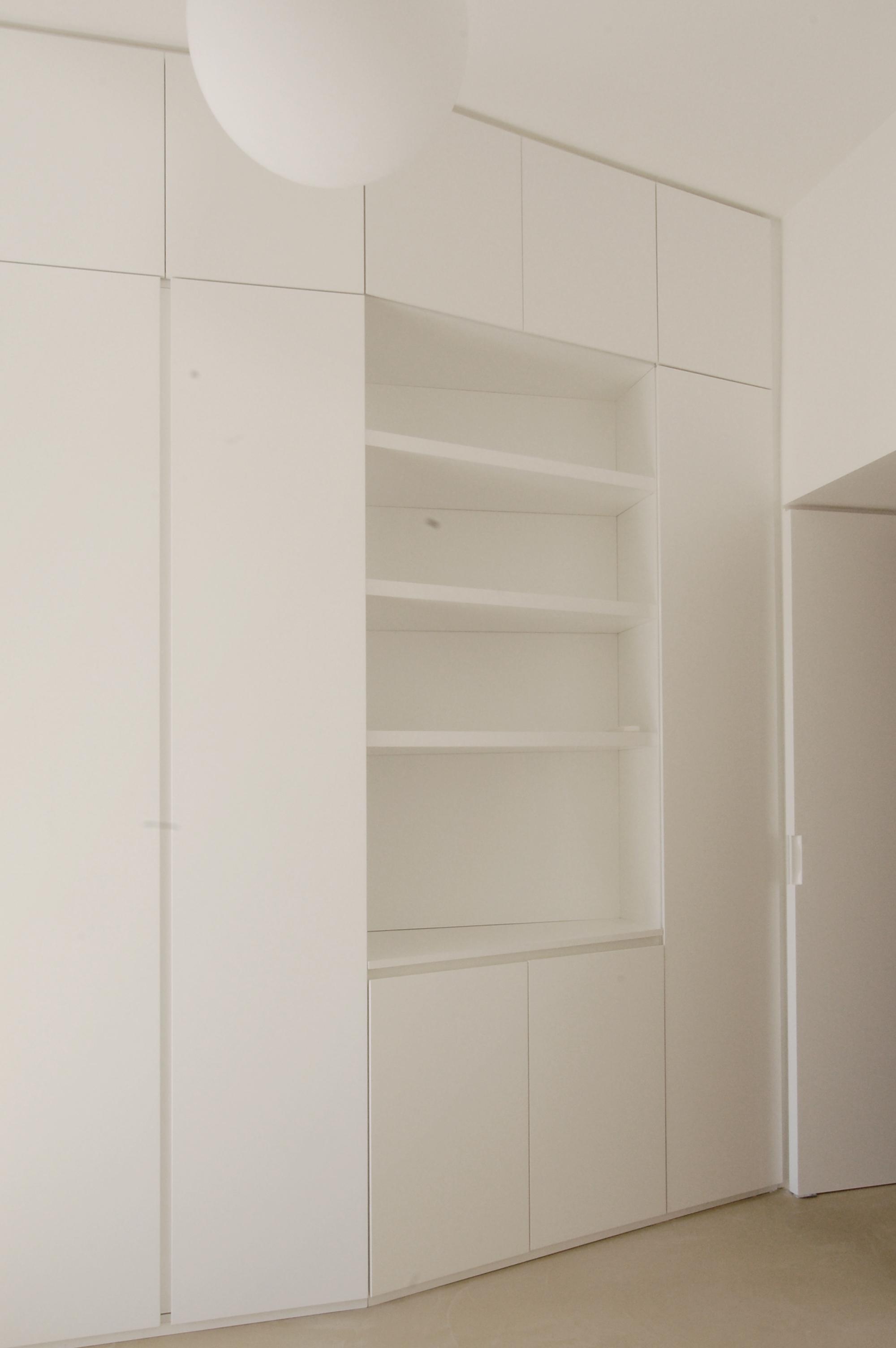 Nella zona notte, una ampia parete attrezzata con armadiatura e libreria risolve le esigenze pratiche e asseconda con il disegno l'accesso alla stanza.