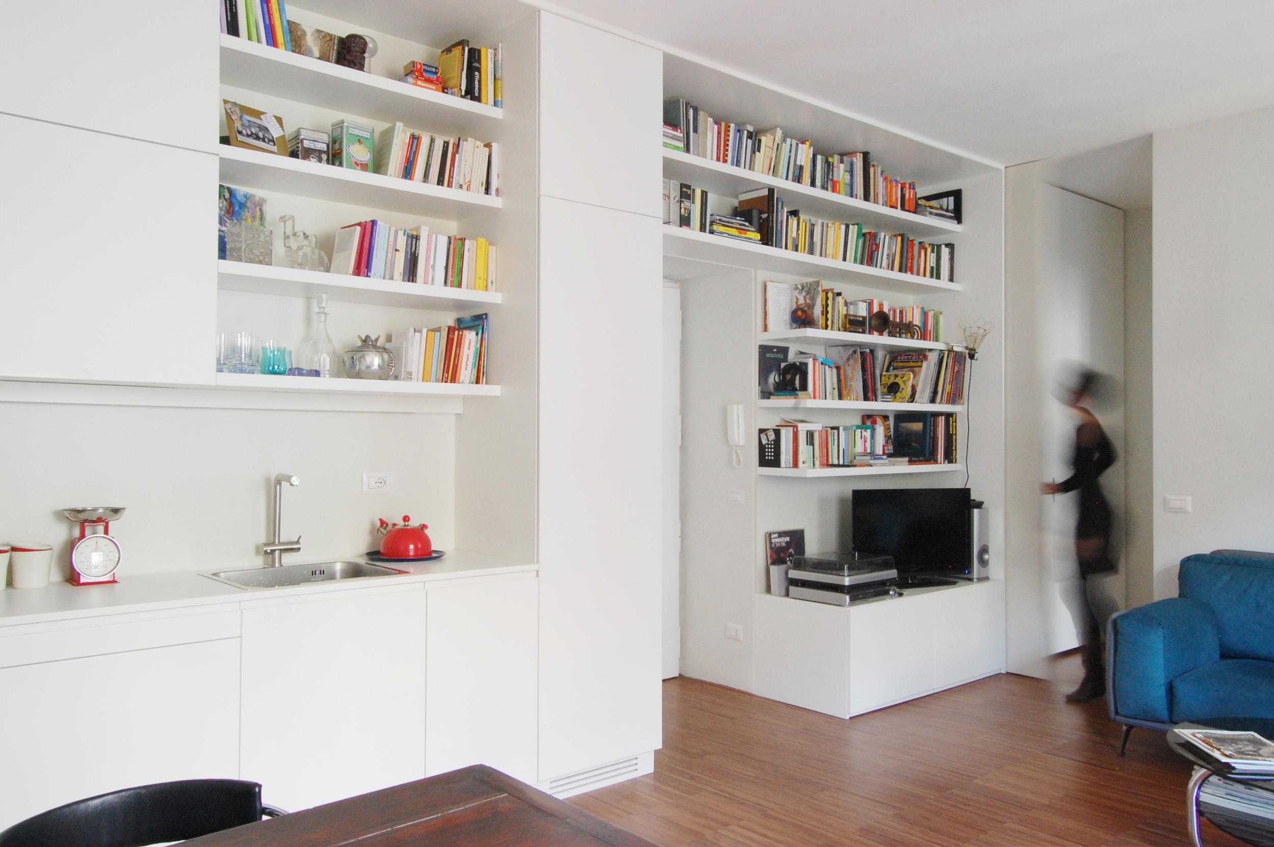 La parete attrezzata che attraversa tutta la casa, divenendo allo stesso tempo libreria, cucina, ripostiglio e armadio per la zona notte.