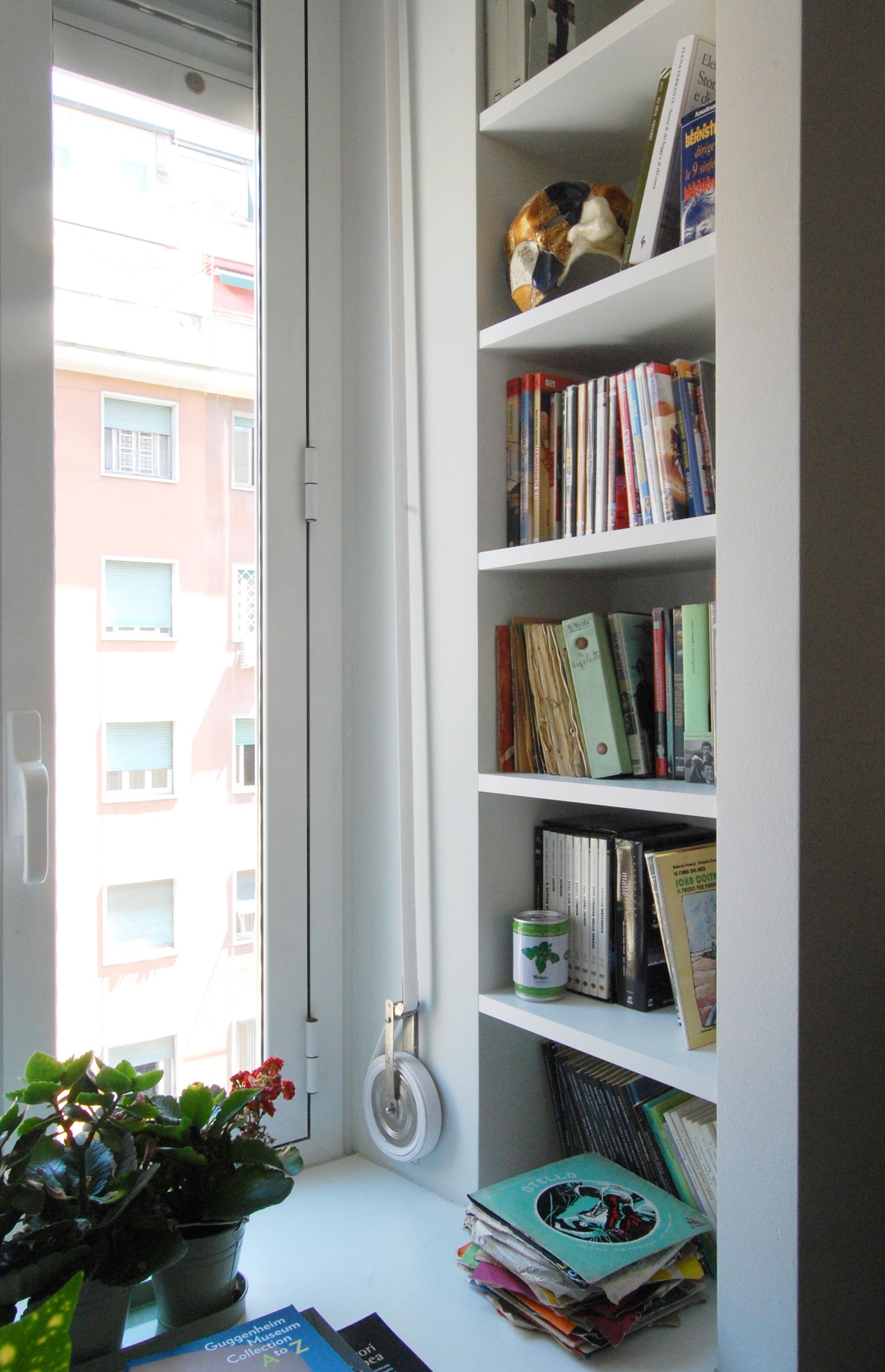 Libri e ricordi di viaggio animano una piccola libreria nella zona living, Ricavata accanto alla finestra, sfrutta una imperfezione nella geometria della muratura perimetrale.