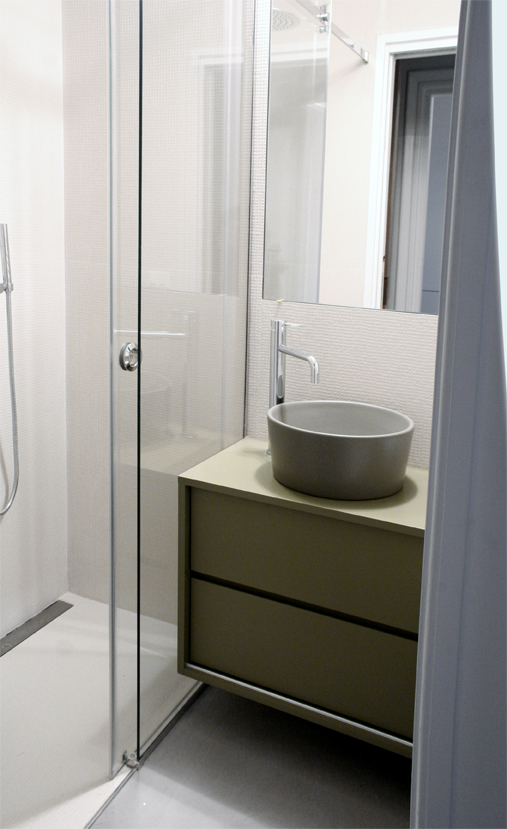 Il bagno, con la luce naturale assicurata dall'apertura vetrata e la cucina che penetra nella doccia, a ricavare lo spazio per i saponi.