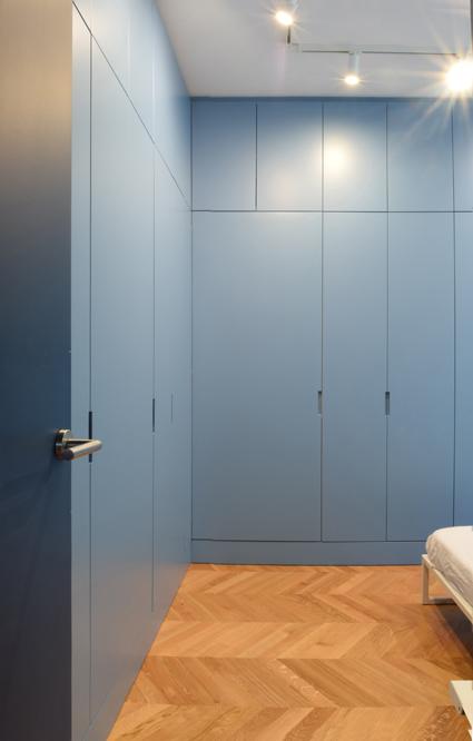 Le ante dell'armadio su misura della camera da letto nascondono l'accesso al bagno privato.