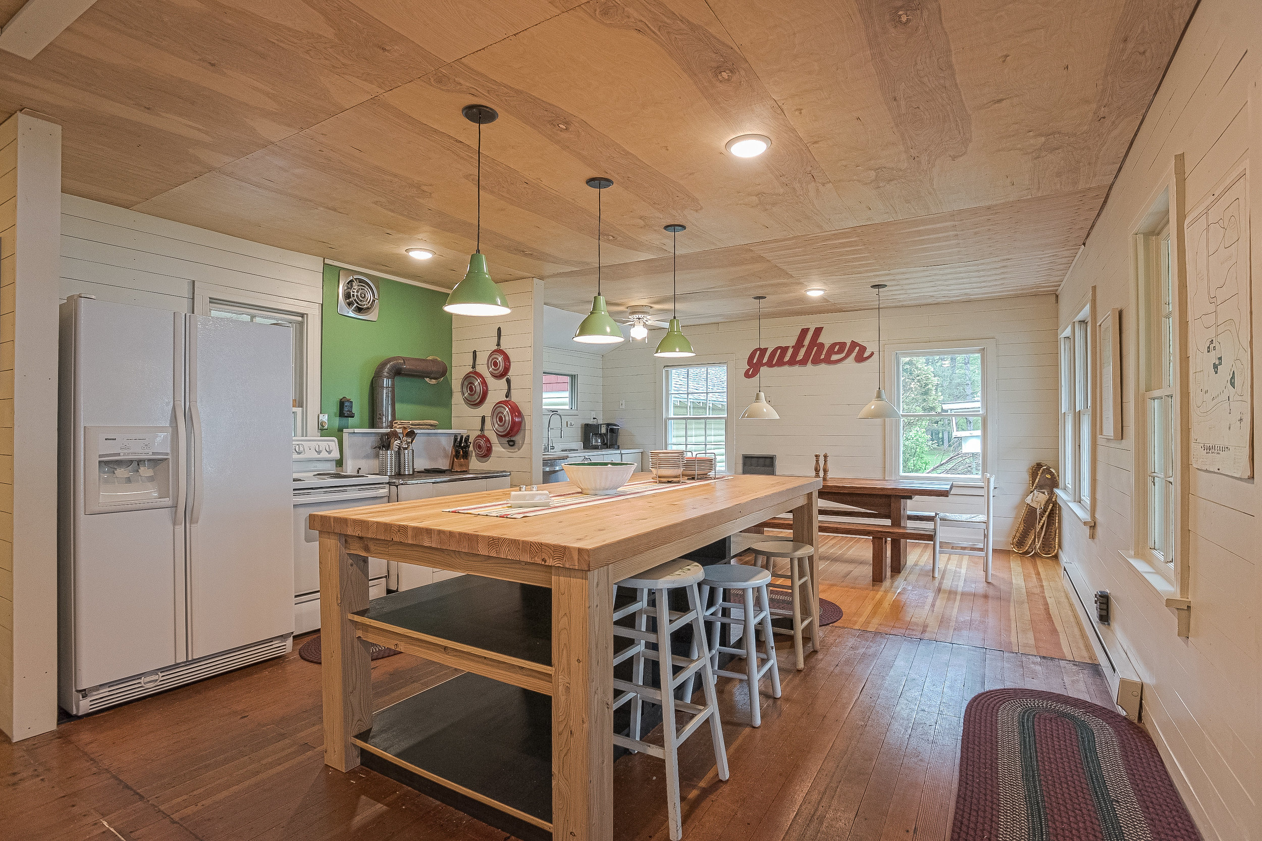 Retro kitchen open to living room with original hardwoods, big butcher block island for staging with plenty of storage and a long dining table for group meals.