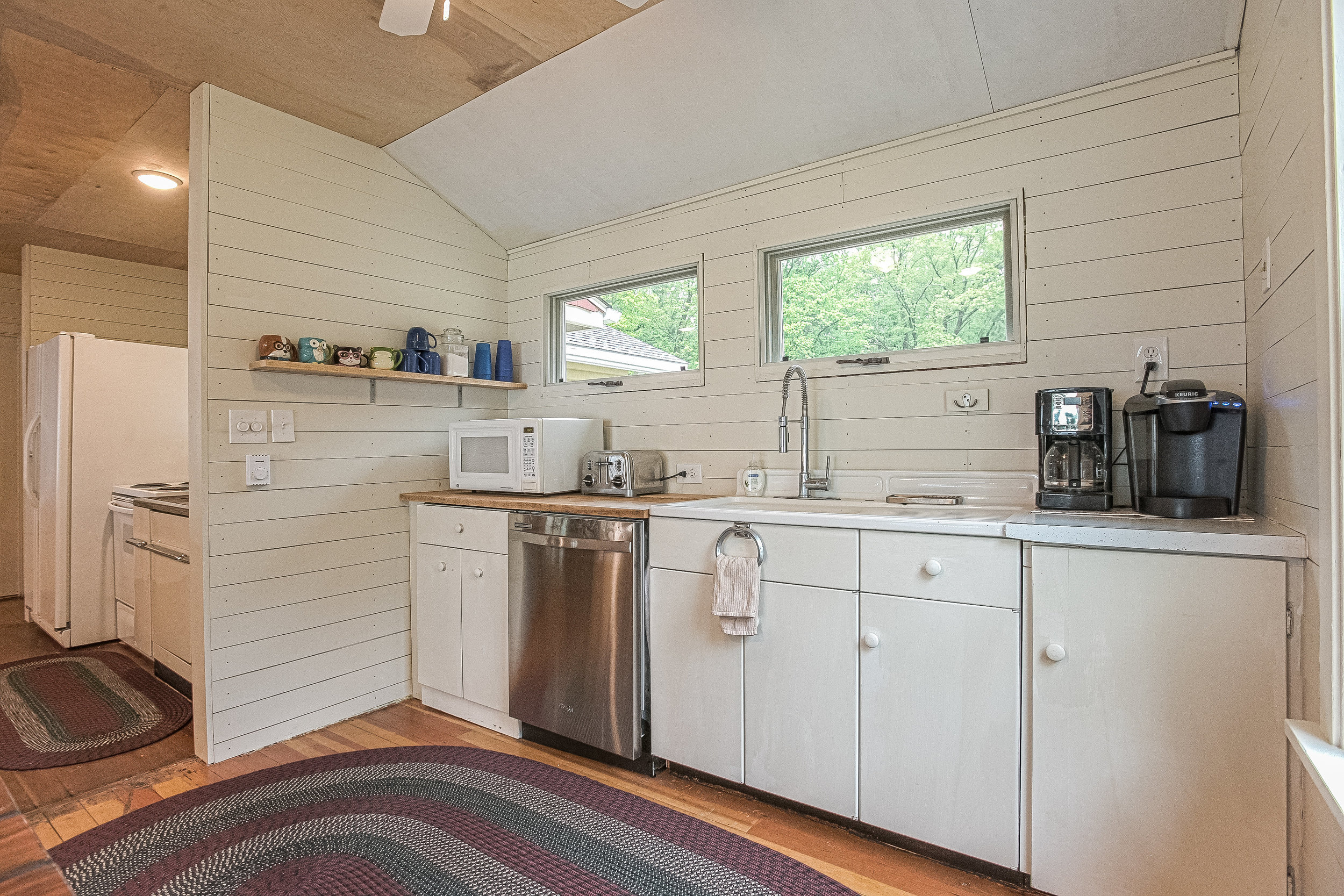 Efficient clean up station with modern dishwasher and vintage farm sink doubles as coffee hub with Keurig, Mr. Coffee and lots of oversized mugs.