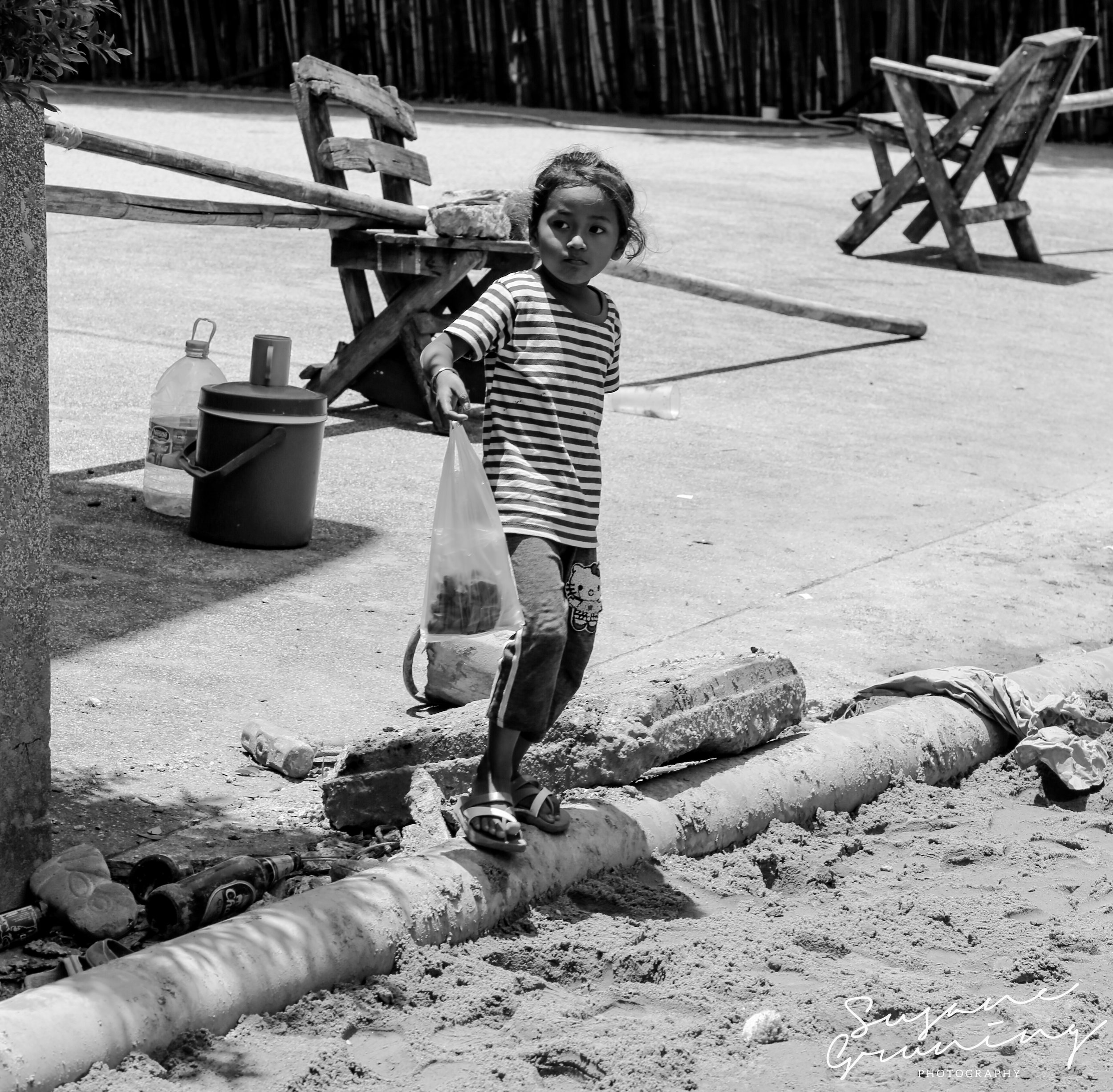Just a girl - A little Thai girl going about her business.