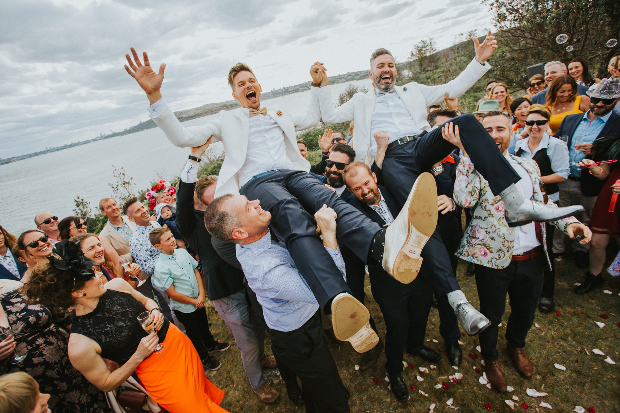A wedding at Qstation with two grooms being lifted by their friends. Everyone's smiling.