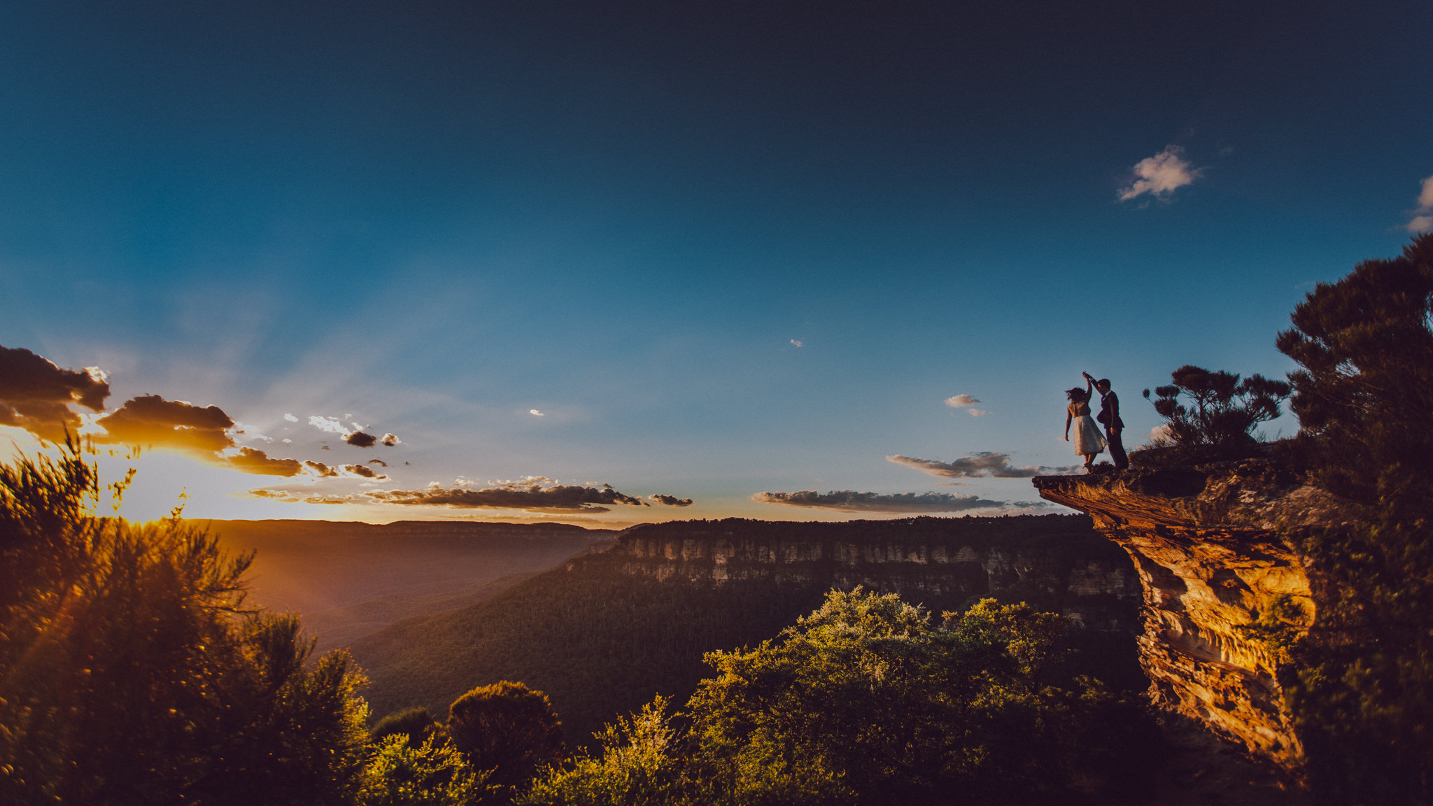 Two newlyweds dancing during a warm sunset on a cliff edge at Lincoln's Rock in the Blue Mountains.