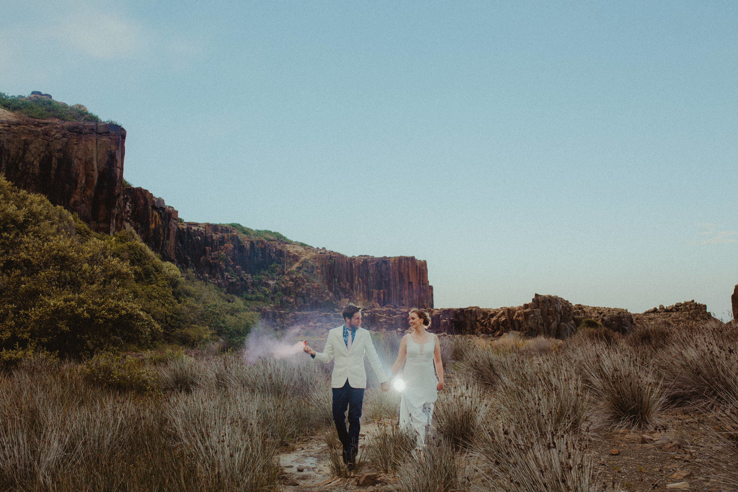 A bride and groom holding hands while holding a flair in a desert type enviroment at bombo quarry, NSW.