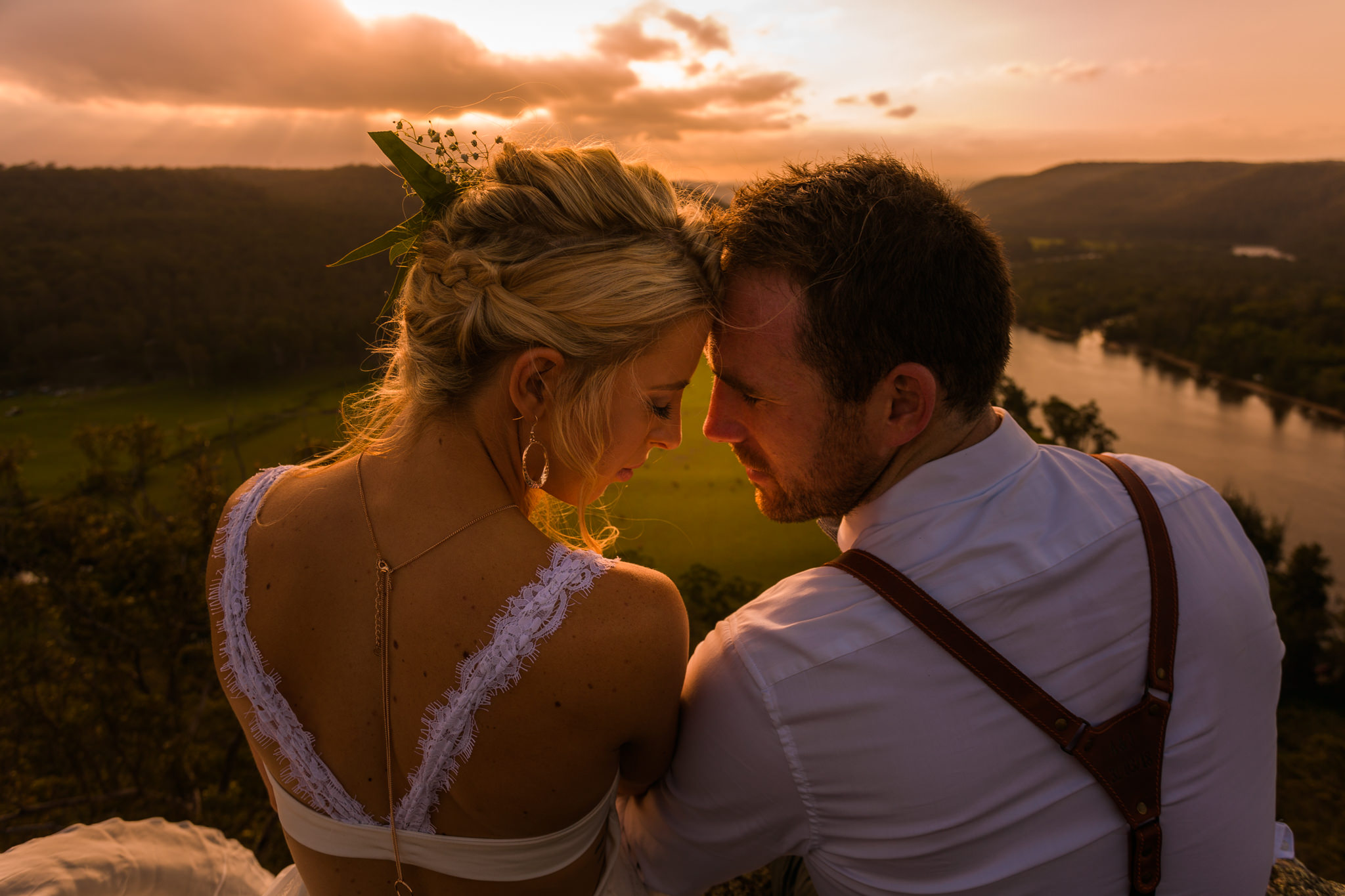 Two newlyweds sitting on top of a cliff, foreheads together looking into eachothers eyes with an orange sunset and river in the background.