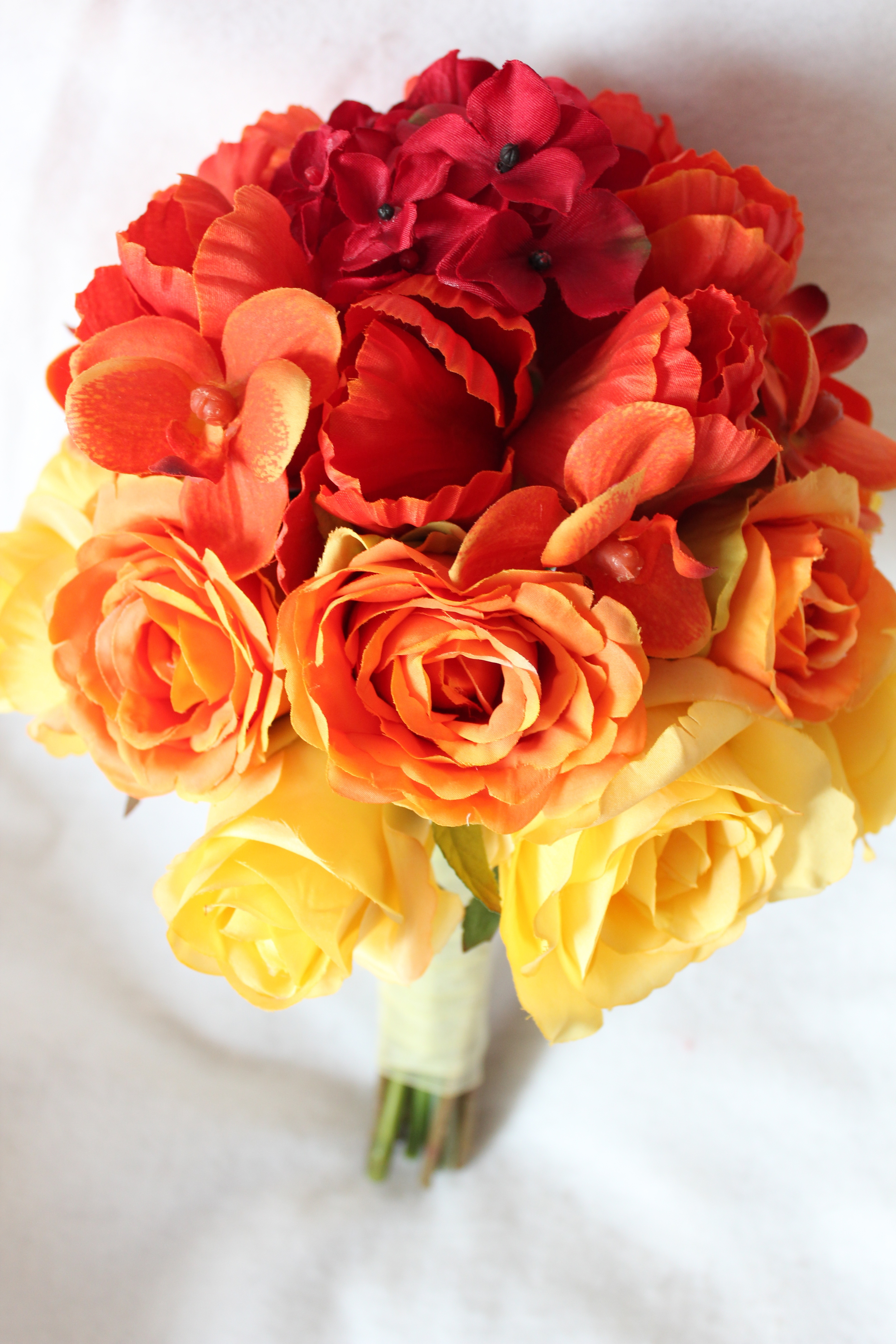 Ombre Silk Bridal Bouquet in yellow and orange Roses, orange orchids and Tulips, and red Hydrangea.
