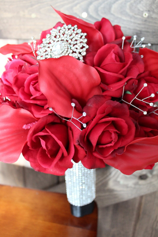 Bridal Bouquet of Fresh Touch Red Roses and Calla Lilies with rhinestone sprays, bouquet jewel and rhinestone wrap on the stems.