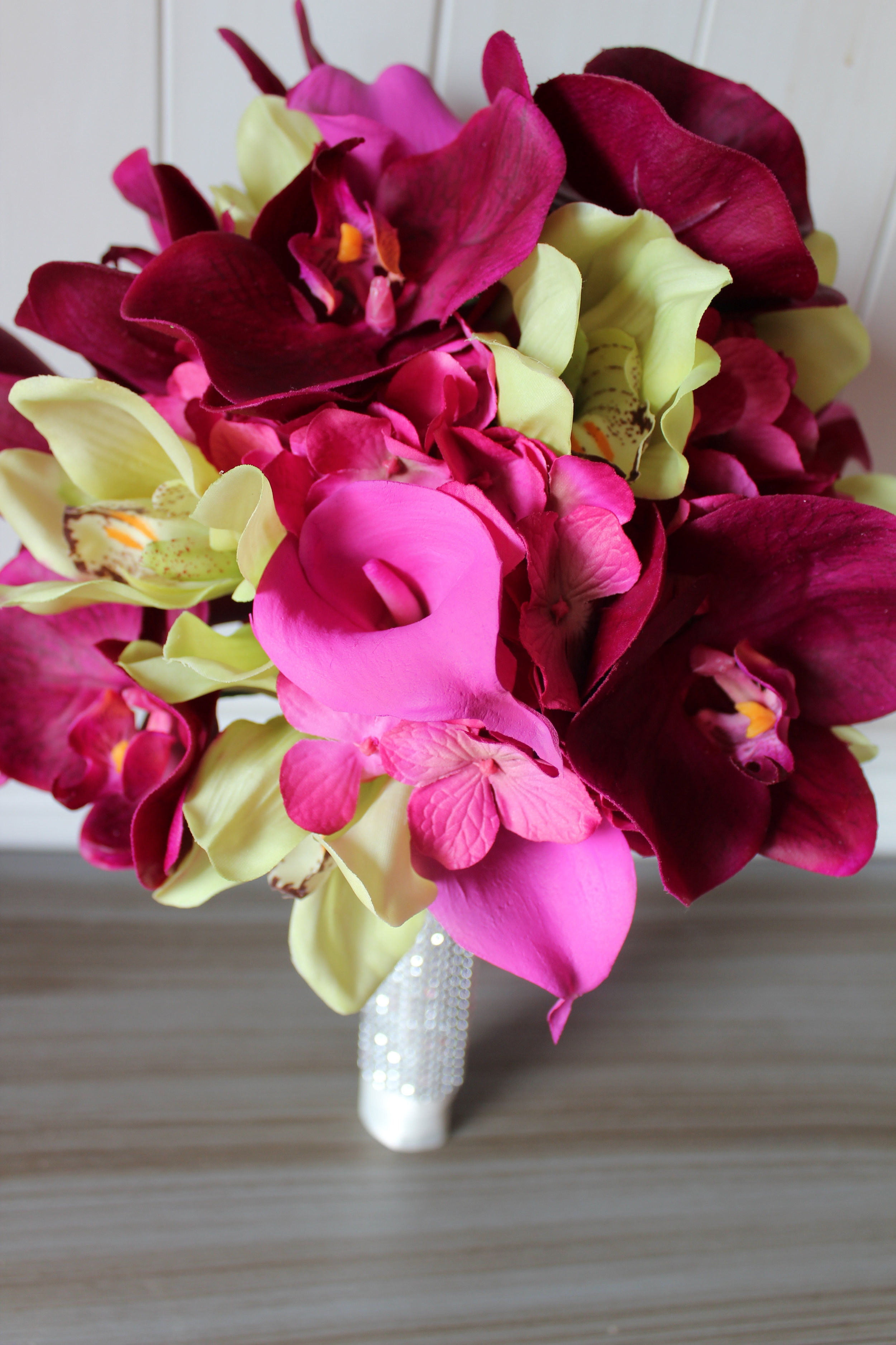 The destination wedding bridal bouquet includes Lime Orchids, Pink Calla Lilies, Pink Hydrangea, and deep pink Orchids.