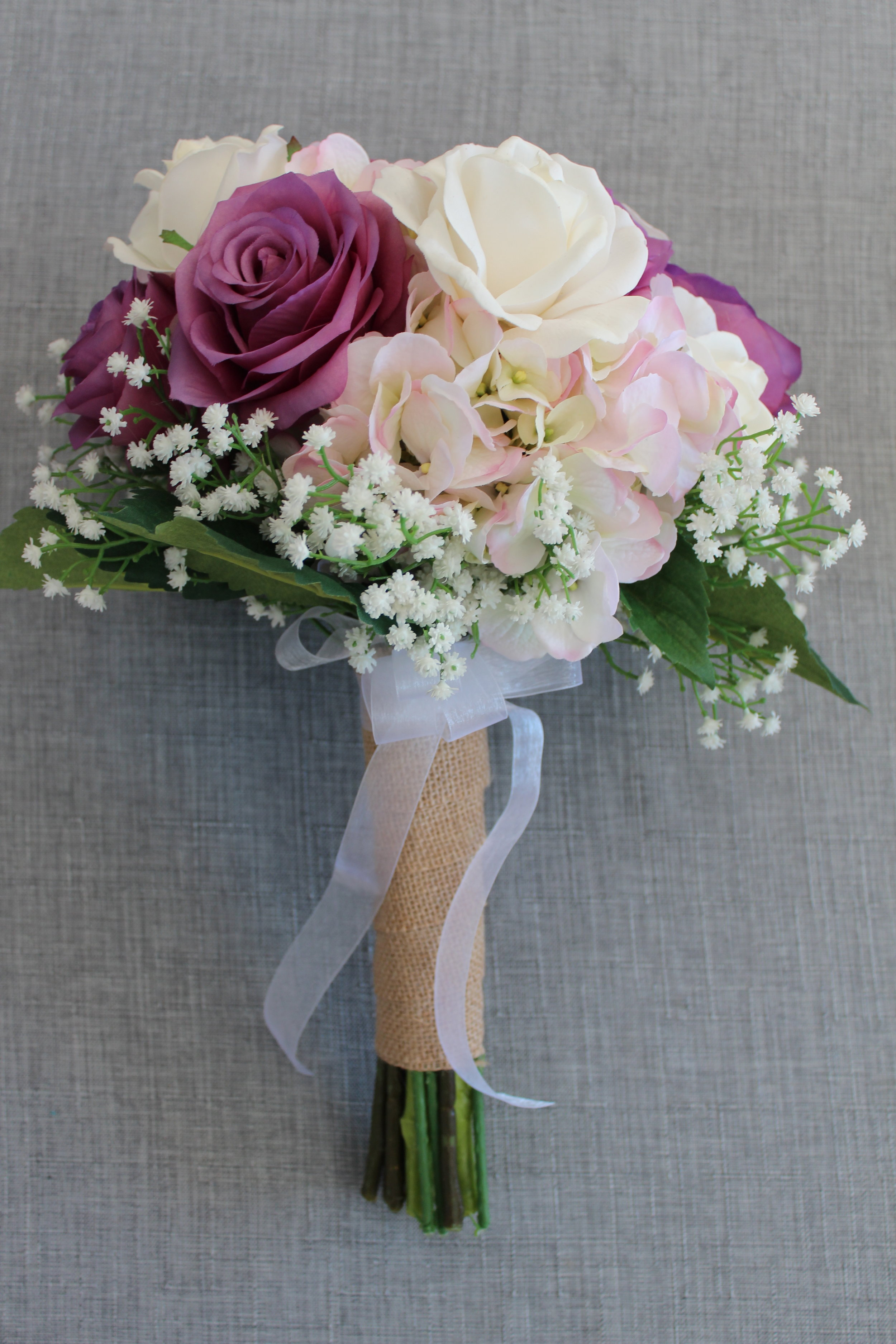 Cream Roses, Lavender Roses, Mauve Hydrangea, Baby's Breath, Hydrangea Leaves, Burlap and Ribbon.